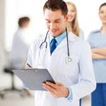 Male doctor writing prescription — Stock Photo