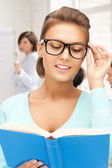 Smiling student girl reading book at school — Stockfoto