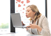 Woman with computer kissing the screen — Stock Photo