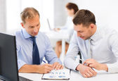 Businessmen with notebook on meeting — Stock Photo