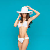 Model posing in white bikini with hat — ストック写真