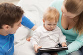 Parents and adorable baby with tablet pc — Stock Photo