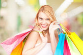 Woman holding color shopping bags in mall — Stock Photo