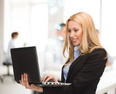 Woman with laptop computer in office — Stock Photo