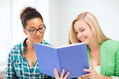 Smiling student girls reading book at school — Stock Photo