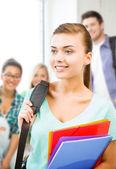 Chica estudiante con mochila y carpetas de color — Foto de Stock