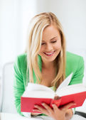 Smiling young woman reading book at school — Stock Photo