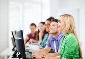 Estudiantes con ordenadores estudiando en la escuela — Foto de Stock
