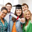 Stock Photo: Student girl in graduation cap with diploma
