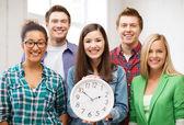 Grupa uczniów w szkole z zegarem — Zdjęcie stockowe