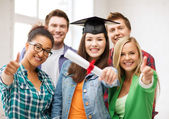 Student girl in graduation cap with diploma — Stock Photo