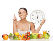Woman with fruits, vegetables and clock — Stock Photo