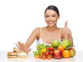 Woman with fruits showing thumbs up — Stock Photo