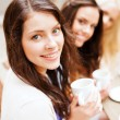 Stock Photo: Beautiful girls drinking coffee in cafe