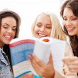 Beautiful girls looking into tourist book in city — Stock Photo