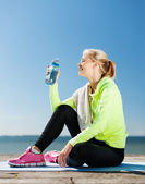 Woman drinking water after doing sports outdoors — Stock Photo