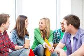 Estudiantes de comunicación y riendo en la escuela — Foto de Stock