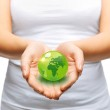 Woman hands holding green sphere globe — Stock Photo #28015539