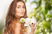Bella mujer con orquídeas phalaenopsis — Foto de Stock