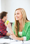 Student girl with green apple in college — Stock Photo