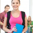 Stock Photo: Smiling student with book and school bag