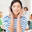 Student girl in big headphones at school — Stock Photo