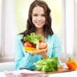 Woman in the kitchen with vegetables — Stockfoto
