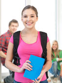 Smiling student with book and school bag — Stock Photo