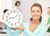 Attractive student pointing at clock — Stock Photo