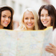 Beautiful girls looking into tourist map in city — Stock Photo #28640481