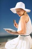 Femme au chapeau, faire des achats en ligne à l'extérieur — Photo