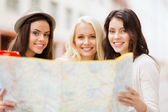 Beautiful girls looking into tourist map in city — Stok fotoğraf