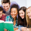 Students reading book at school — Stock Photo