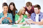 Studierende auf der suche auf smartphones und tablet pc — Stockfoto