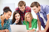 International students looking at laptop at school — Stock Photo