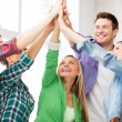 Stock Photo: Happy students giving high five at school