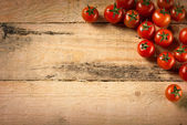 Cherry tomatoes on wood background — Stock Photo