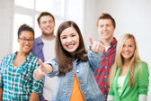 Students showing thumbs up at school — Stock Photo