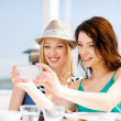 Stock Photo: girls taking photo in cafe on the beach