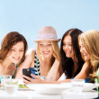 Girls looking at smartphone in cafe on the beach — Stock Photo #28874021