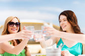 Girls making a toast in cafe on the beach — Stock Photo