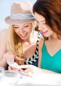 Girls looking at smartphone in cafe — Stock Photo