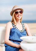Flicka i nyanser i café på stranden — Stockfoto