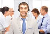 Helpline operator with headphones in call centre — Stock Photo