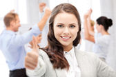 Businesswoman showing thumbs up in office — Stock Photo