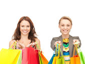 Attractive girls holding color shopping bags — Stock Photo