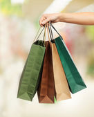 Woman hands holding shopping bags — Stock Photo