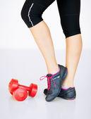 Piernas de la mujer deportivo con luz rojas mancuernas — Foto de Stock
