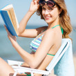 Stock Photo: Girl reading book on beach chair