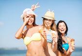Tjejer i bikini med glass på stranden — Stockfoto